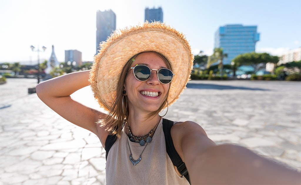 A Young Happy Woman In The City Wearing A Hat And Sunglasses Taking A Selfie