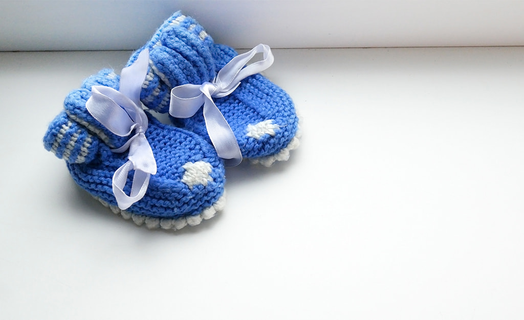 Blue Crochet Baby Shoes With White Bows On A White Background