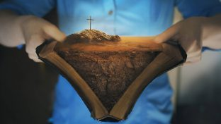 Closeup Composite Of Woman Holding Bible Open With Packed Dirt Between The Pages And a Cross Emerging From The Top