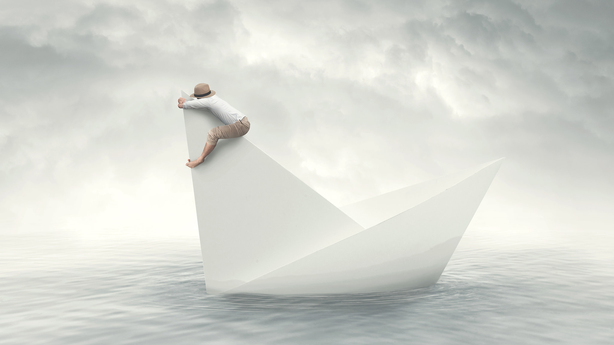 A Conceptual Image Shows A Paper-Like Sailboat In The Water With A Man Clinging To The Topmost Sail Against A Gray Cloudy Sky
