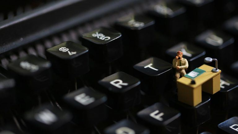 Zoomed In View Of A Black Keyboard With A Tiny Desk And Person Sitting At The Desk On One Of The Keys Signifying Workplace Loneliness And Isolation
