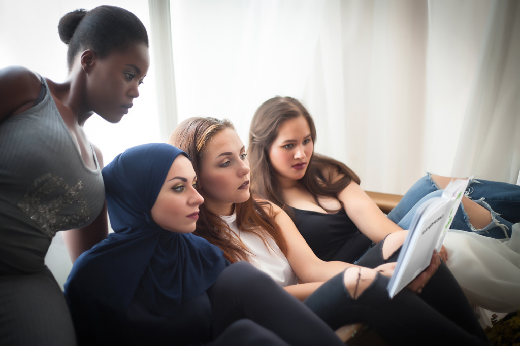 4 Ethnic And Culturally Diverse Women All Reading From The Same Book