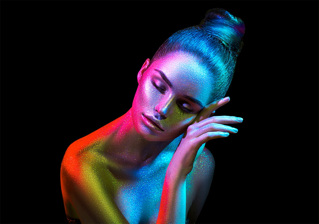 Image Of An Attractive Woman In Metalic Makeup And Bodypaint Of Different Colors Against A Black Background