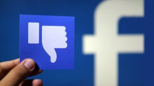 """Photograph Of Hand Holding Small Card With """"Thumbs Down"""" Sign With Part Of Facebook's Logo Blurred In The Background"""