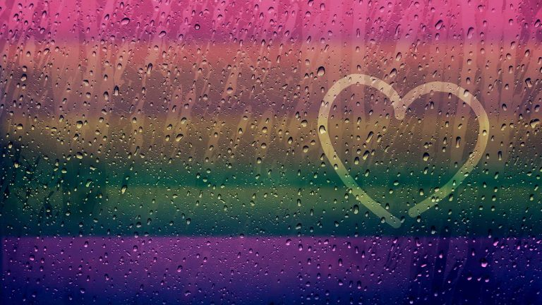 Finger-Drawn Heart Shape On Rainy Window Surface With A Rainbow Cast