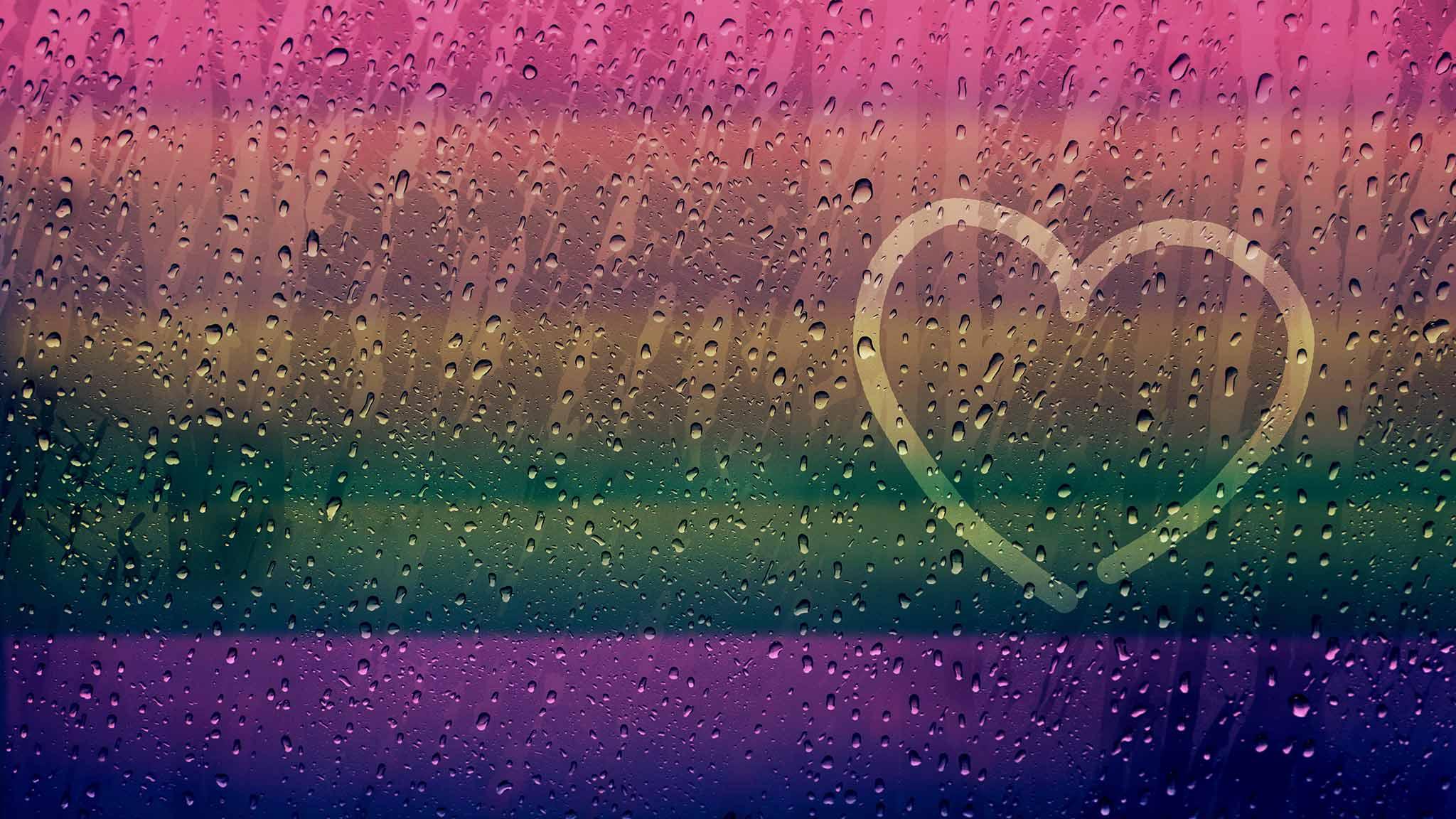 Finger-Drawn Heart Shape On Rainy Window Surface With A Rainbow Cast