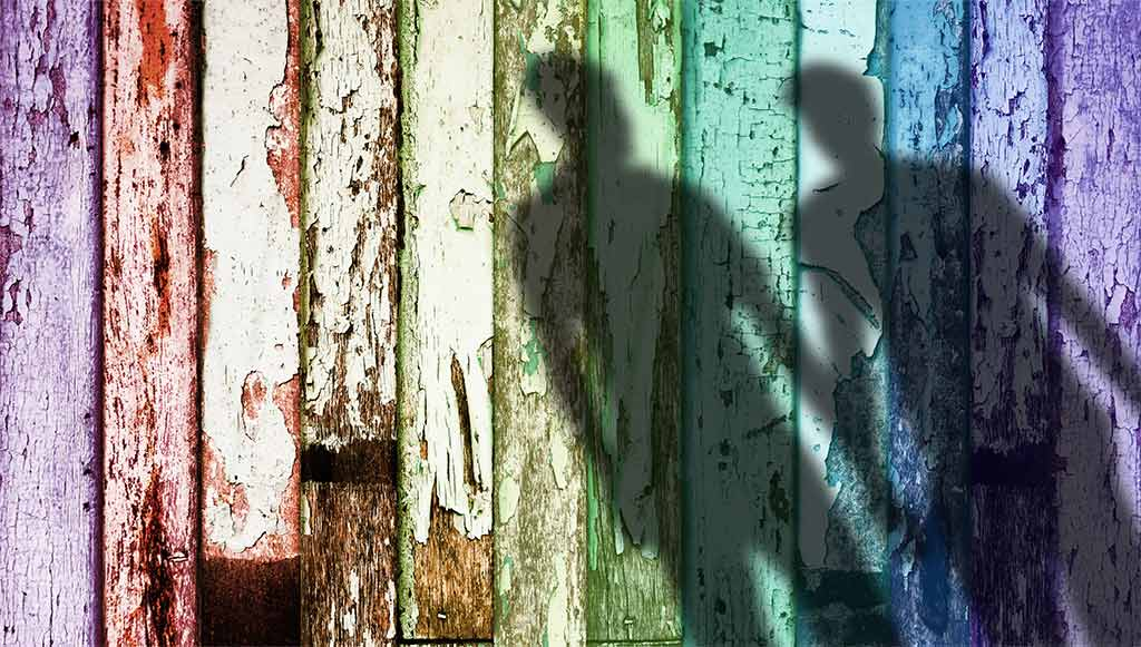 Shadow Of Two Men Holding Hands Stretches Across A Weathered, Rainbow-Painted Fence