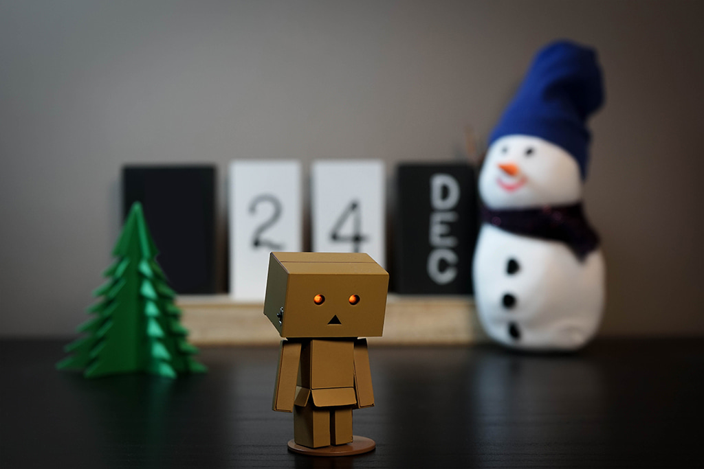 A Small Cardboard Robot With Sad Expression Stands On Tabletop In Front Of Dec. 24 Calendar And Holiday Decorations