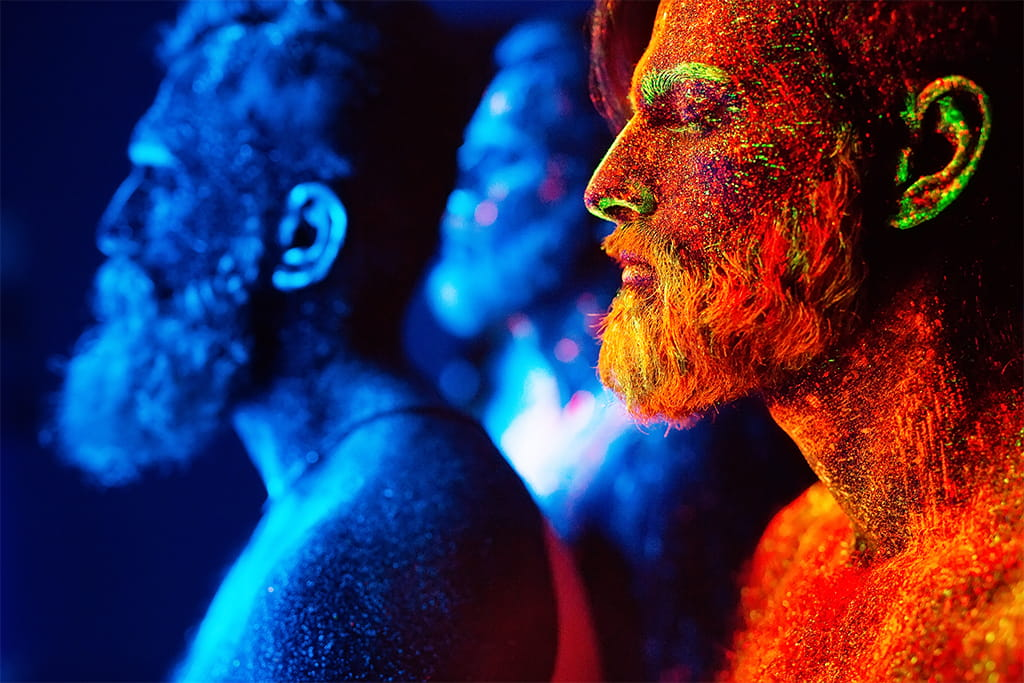 Image Of Three Men In Ultraviolet Powder, Two Blue And One In Red