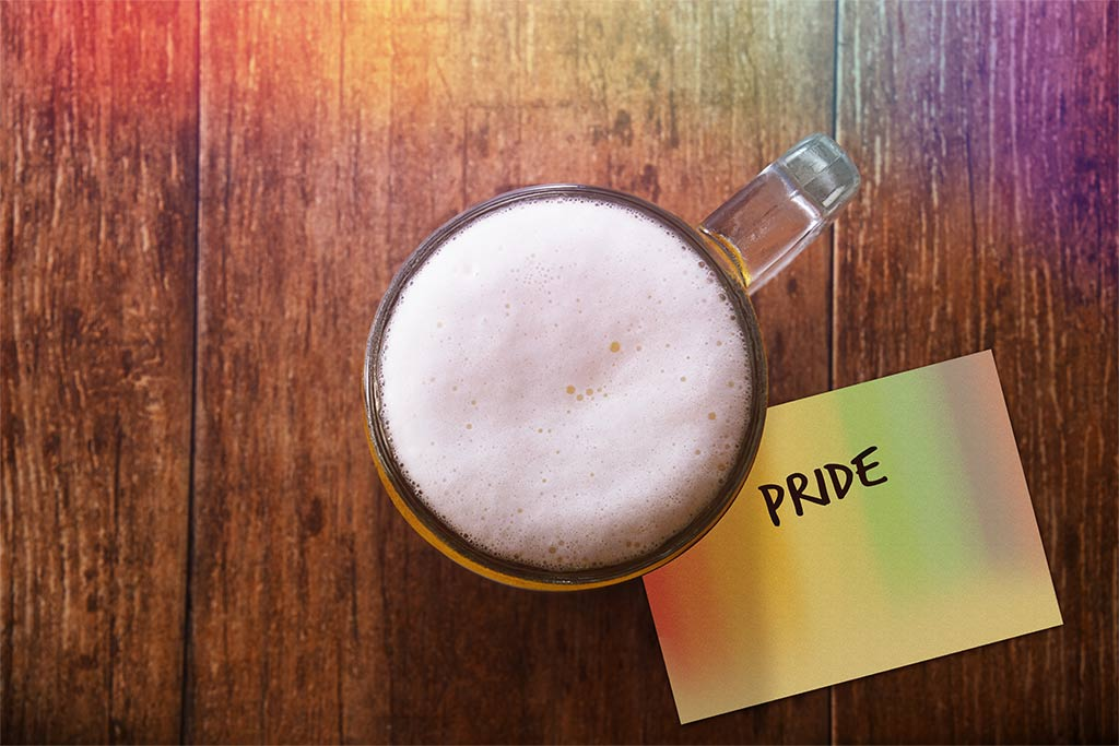 """Aerial View Of Full Beer Mug Resting On Yellow Post-It Note That Reads """"PRIDE"""""""