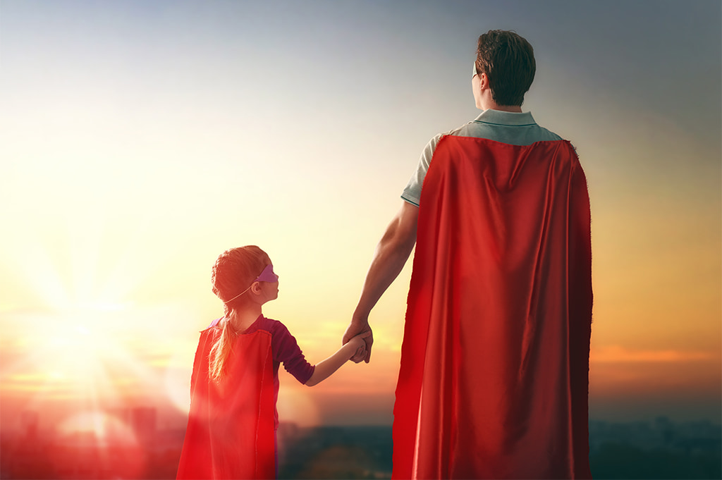 Image Of A Man Holding His Young Daughter's Hand Both Wearing Super Hero Capes Looking At The Sunrise