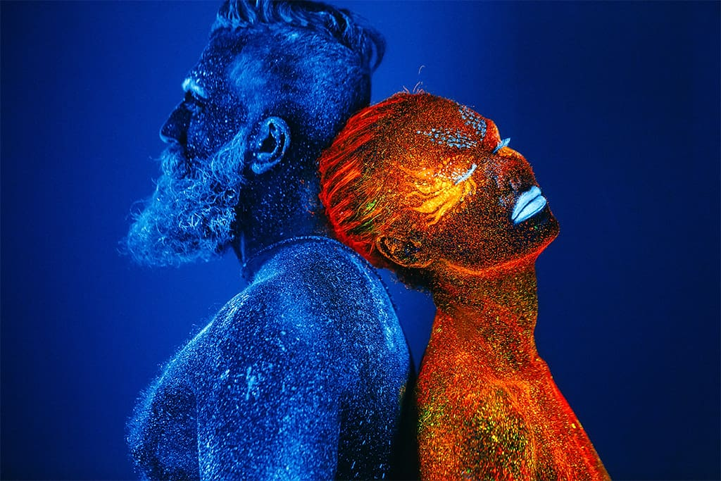 Image Of A Couple In Ultraviolet Powder With A Bearded Man And Woman In Red Standing Back To Back