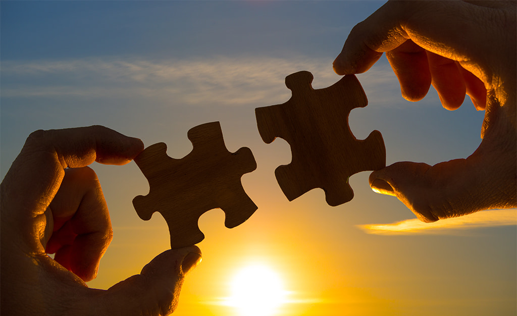 Hands Holding Up Two Puzzle Pieces That Fit Together Against A Setting Sun Background