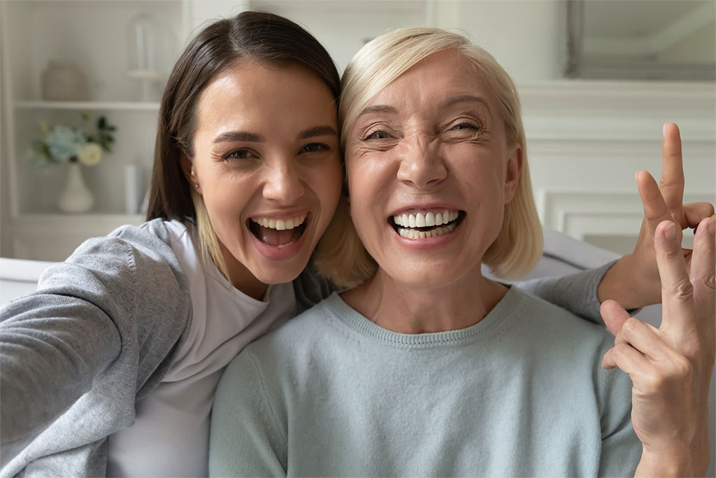 Young Woman And Elderly Woman Smiling And Posing For A Selfie Together