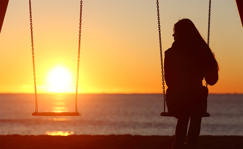 Silhouette Of A Woman Sitting On A Swing At Sunset Looking At An Empty Swing Beside Her That Symbolizes Loss