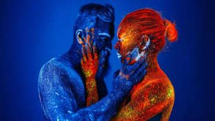 Bearded Man In Blue And Woman In Red In Ultraviolet Powder Looking Into Each Other's Eyes Signifying A Soulmate Or Twin Flame