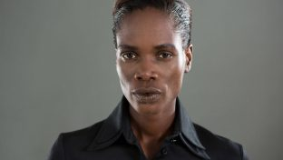 An African American Androgynous Person Wearing A Black Collared Shirt With A Serious Look On Their Face