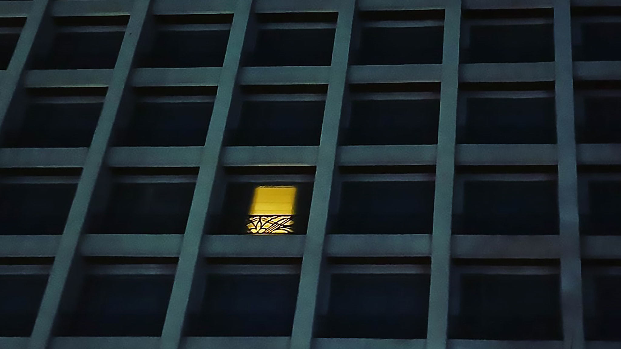 A Close Up Of A Large City Apartment Building With All Lights Out Except One Apartment