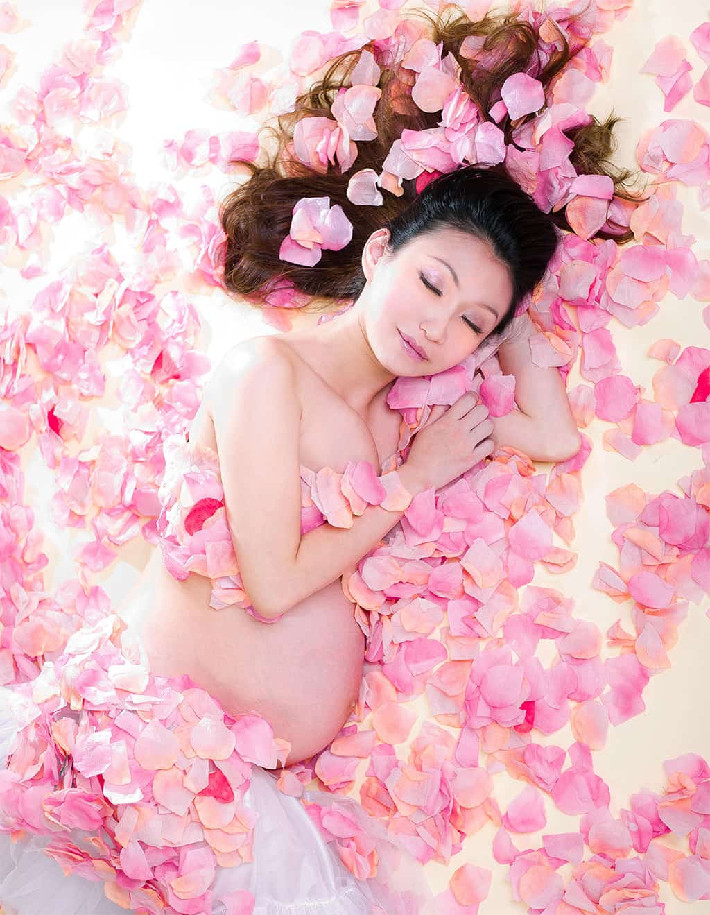 Photo Of A Pregnant Asian Woman Sleeping With Rose Petals All-Around Her