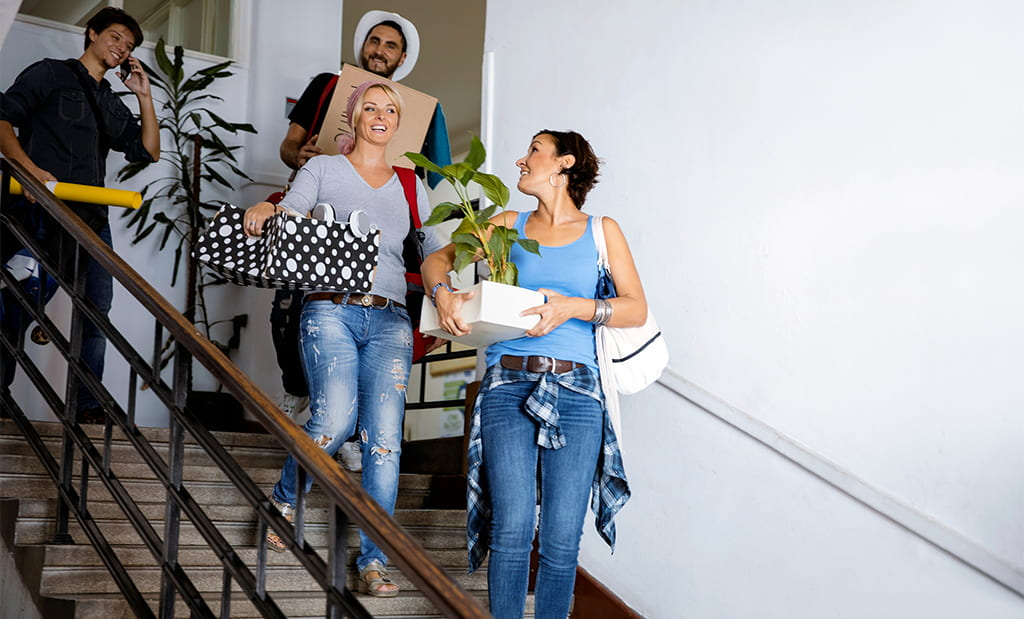 College Students Appearing Happy And Social As They Carry Belongings Down Steps To Move Into The Dorm
