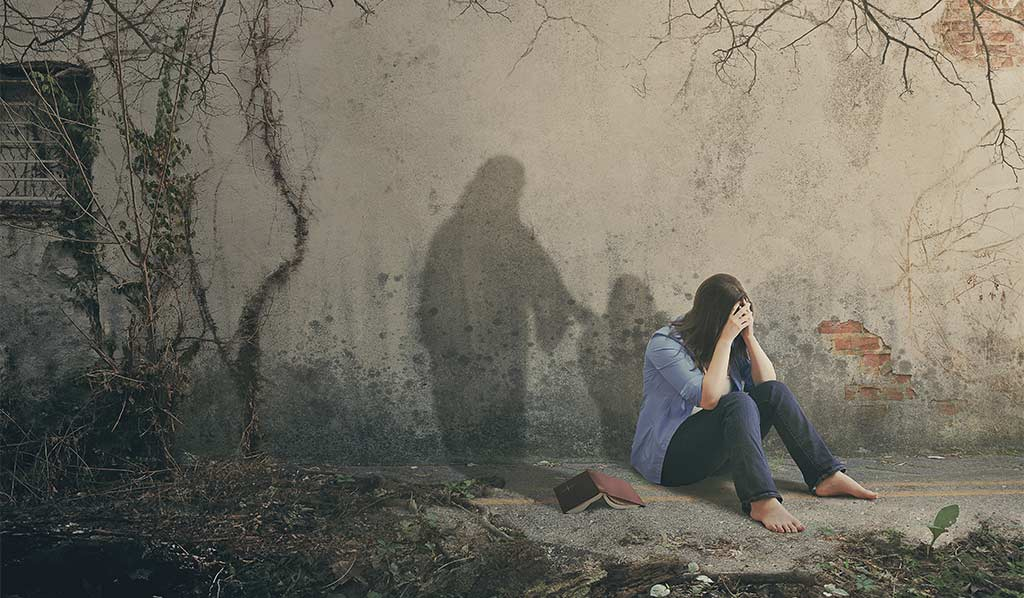 Composite Of Woman Sitting On Ground, Head In Hands, Being Comforted By The Shadow Of Jesus