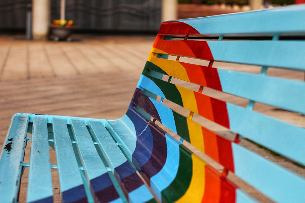 Closeup Of Empty Blue Bench With Rainbow Painted Across It, Loneliness Concept