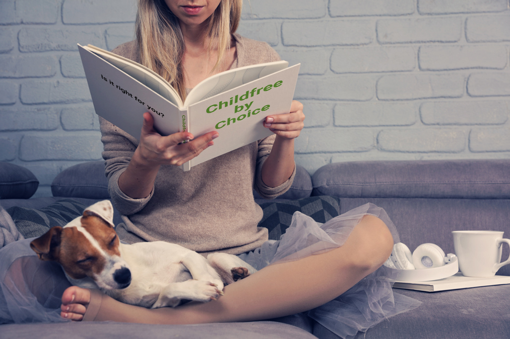 """Woman Sitting On A Couch With A Dog Sleeping Peacefully In Her Lap Reading A Book Titled: """"Childfree By Choice"""""""